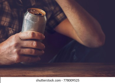Man drinking a cold beer after work in the evening. Hand holding a aluminum can. Resting time in the bar or pub. Thoughtful atmosphere. Alcohol problem concept.