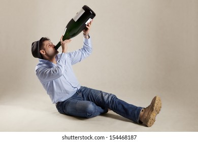 Man drinking from extremely big bottle, studio shot