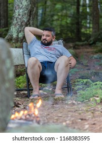 A man is drinking front of a burning camp fire