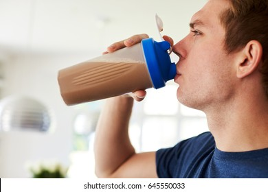 Man Drinking Protein Shake In Kitchen At Home
