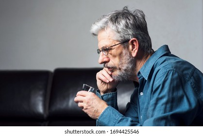 Man drinking and using phone at home alone