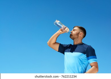 Man Drinking Water After Running. Portrait Of Handsome Athletic Male In Colorful Sportswear Resting After Fitness Workout, Drink Water From Bottle On Blue Sky Background. High Quality Image.
