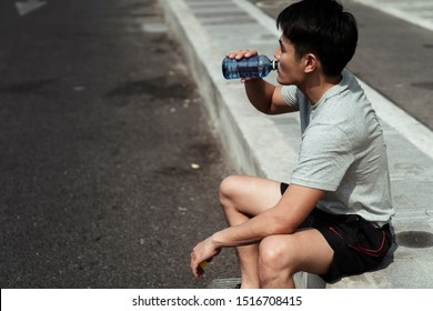 Man drinking water from bottle after running.