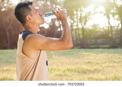 Man drinking water from bottle after running in a park