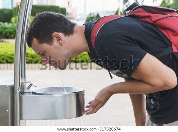 Man drinking water from drinking fountain at street.