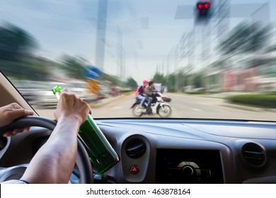 Man drinking while driving, motion image of accident on the road as background.