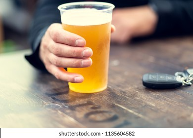 Man drinks beer and car keys are on the table. Concept of driving a car after alcohol consumption.