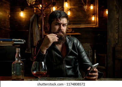 Man drinks brandy or whiskey. Bearded man wearing suit and drinking whiskey brandy or cognac. Sommelier tastes alcohol drink. Drinking and party concept. Degustation and tasting