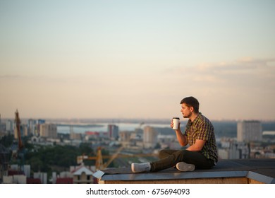 A man drinks coffee early in the morning on the roof. He looks into the distance and reflects. In the background, the city landscape