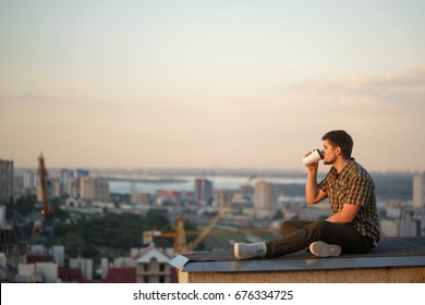 A man drinks coffee early in the morning on the roof. He looks away and thinks. In the background, the city landscape