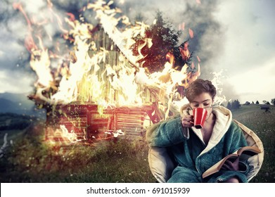 Man drinks coffee and reading a book while his house is on fire, on a mountain background. Concept of a careless man.