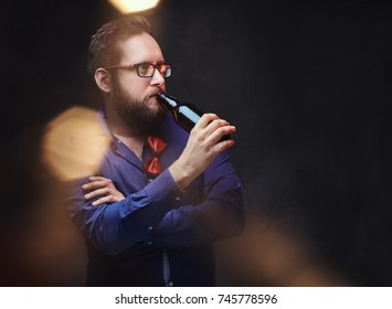 A man drinks craft beer from a bottle.