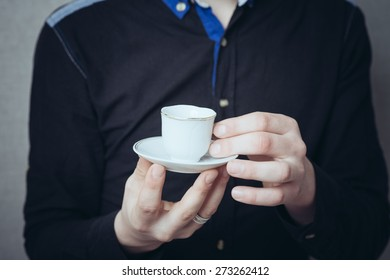 A man drinks tea or coffee, holding a small white cup. On a gray background