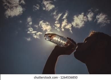 A man drinks water from a plastic bottle outdoors
