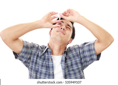 Man dripping eye with eyes drops.