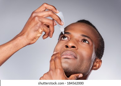 Man dripping eye. Young African man applying eye drops while standing against grey background