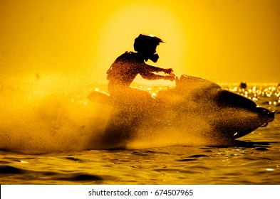 man drive jet ski at sunset.