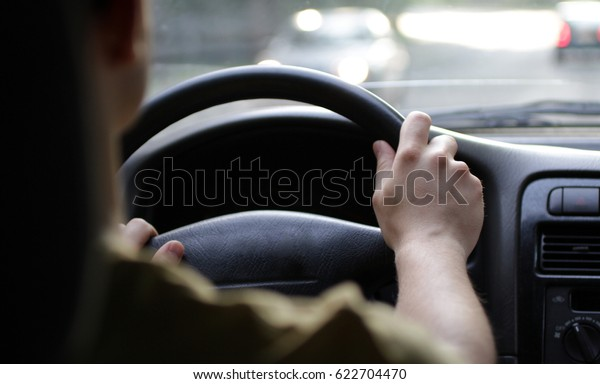man driver hands on helm driving by car