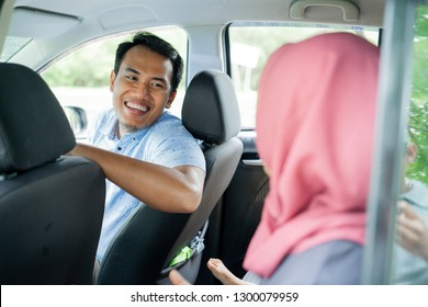 man driver looks smile and happy chatting with a hijab passenger on the seat back