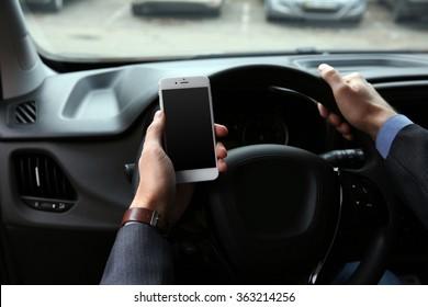 Man driver using smart phone in car