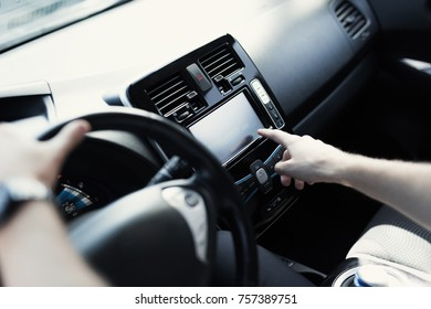 A man drives an electric vehicle. In the frame you can see his hands. He keeps the steering wheel of the car. He presses the control buttons. This is a modern comfortable car.