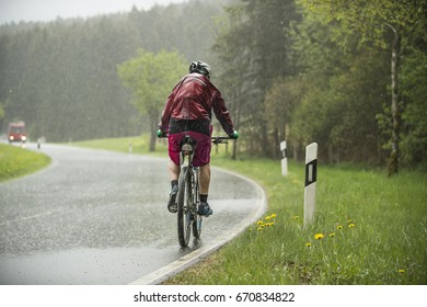 Man drives on the bicycle in the rain