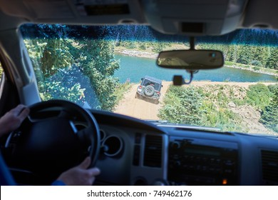 Man driving a 4WD along a dirt road following a friend in a second vehicle as they approach a mountain lake in a first person perspective
