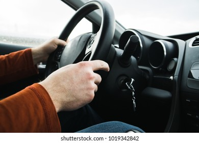 Man driving a car. detail on hands holding steering wheel.