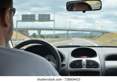 Man driving a car with a dirty front glass after a long drive on a highway with roadsigns and a viaduct  in front of him