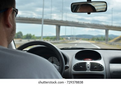Man driving a car with a dirty front glass after a long drive on a highway with a viaduct in front of him