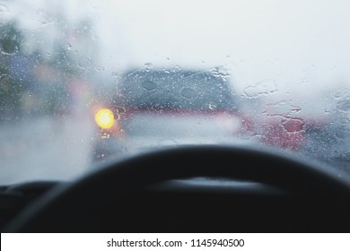 man driving car, hand on steering wheel, looking at the road ahead, selective focus on hand with shallow depth of field.  (Security Equipment concept)