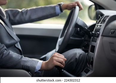 man driving car with hand on gearbox