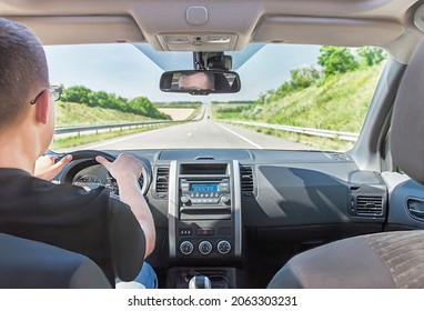 Man is driving car with hands on the steering wheel. Long highway (highroad) is in sunny summer day. Active caucasian male model. Travel (vacations), rental, adventure concept. Selective focus.