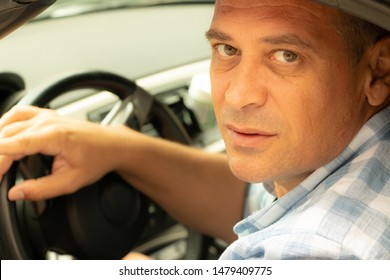 Man driving a car and look thorough a window