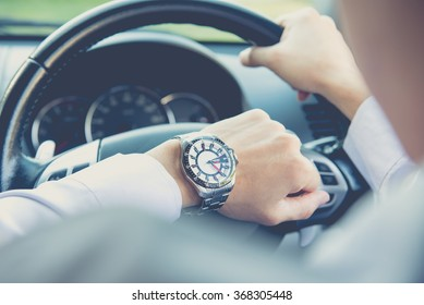 Man driving a car and looking at watch ,business concept ,vintage tone