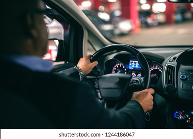 Man driving car at night, hands on wheel. Picture taken from backseat.