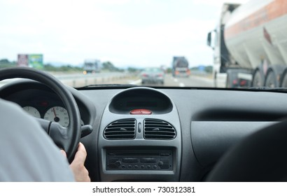 Man driving a car on a highway in traffic jam time and with other vehicles blurred next his car