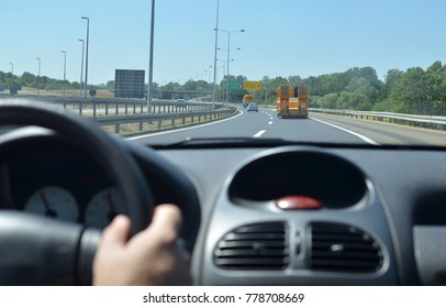 Man driving a car on a highway with other vehicles and direction signs in front of him. Blurred car interior.