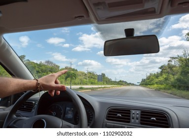 Man driving car on mexican highway, car inside view