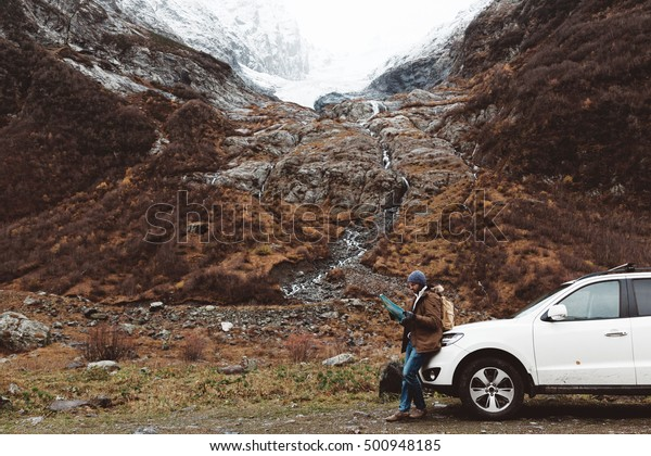 Man driving car on to the mountains. Traveler with backpack looking map. Hiking in cold weather.