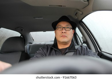 Man driving a car on a rainy day.
