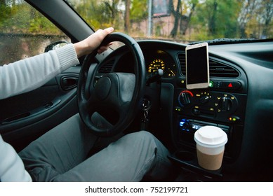 man driving car phone on holder and cup of coffe in cup holder inside in car