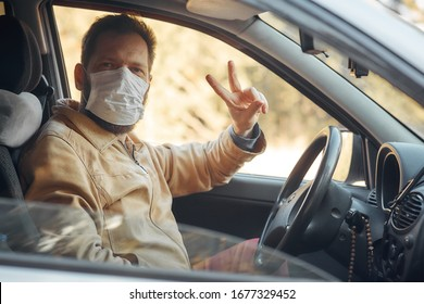 a man driving a car puts on a medical mask during an epidemic, a taxi driver in a mask, protection from the virus
