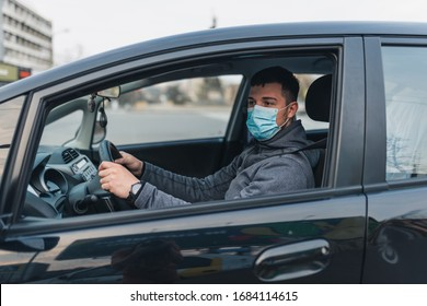 a man driving a car puts on a medical mask during an epidemic, a taxi driver in a mask, protection from the virus. Driver in black car. coronavirus, disease, infection, quarantine, covid-19