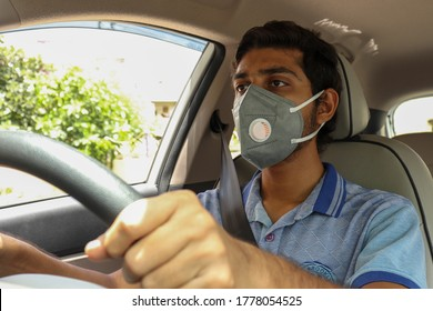 A man driving car puts on a medical mask for protection during Covid 19 or coronavirus pandemic. A taxi driver in mask, protection from virus infection disease.