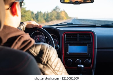 Man driving a car in rural area, backseat view. Male driver in modern vehicle on the road on a sunny afternoon