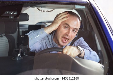 Man driving a car shocked about to have traffic accident, windshield view. Scared funny looking young man driver in the car. Human emotion face expression.