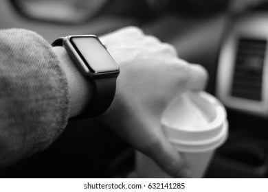 man driving a car with smart watch on the hand