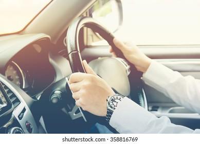 man driving car, steering wheel of a car, vintage color tone, focus at finger