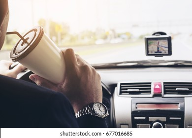 Man driving car using navigator and holding coffee cup